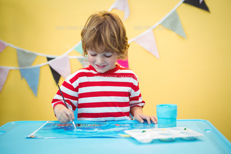 Smiling boy painting a pictureの写真素材 [FYI00486356]