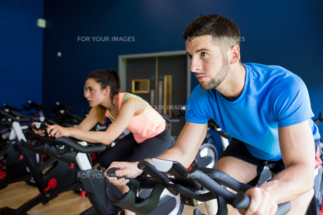 Focused man and woman on exercise bikesの素材 [FYI00486373]