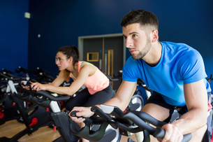 Focused man and woman on exercise bikesの写真素材 [FYI00486373]
