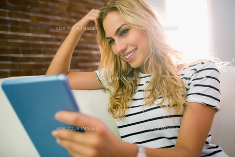 Pretty blonde using tablet on couchの素材 [FYI00486379]
