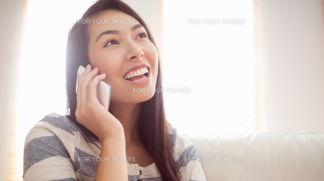 Smiling asian woman on couch using phoneの素材 [FYI00486385]