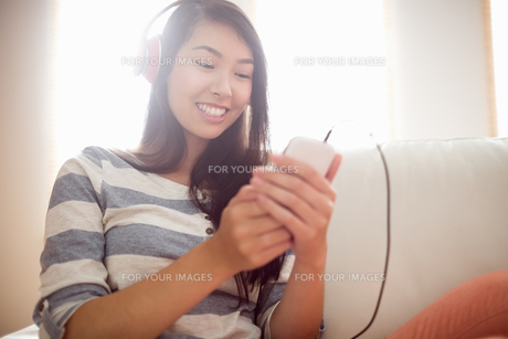 Smiling asian woman on couch listening to musicの写真素材 [FYI00486389]