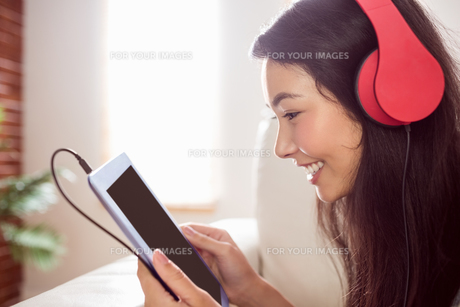 Smiling asian woman on couch listening to musicの写真素材 [FYI00486390]