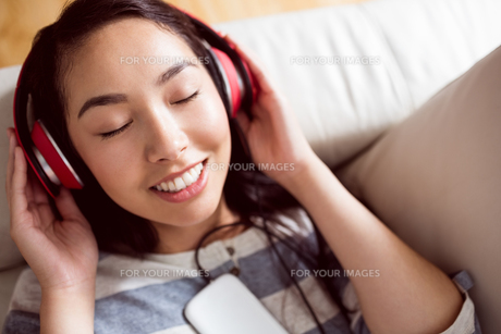Smiling asian woman on couch listening to musicの写真素材 [FYI00486391]