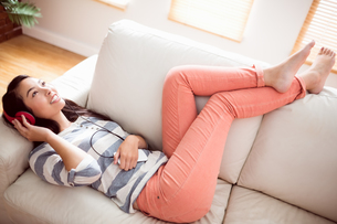 Smiling asian woman on couch listening to musicの写真素材 [FYI00486392]