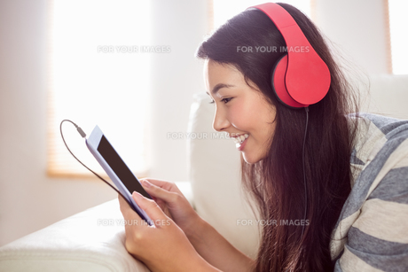 Smiling asian woman on couch listening to musicの写真素材 [FYI00486395]