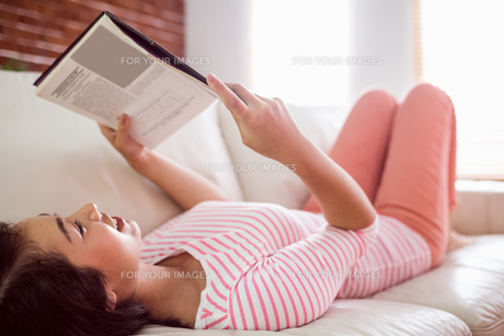 Smiling asian woman on couch readingの写真素材 [FYI00486400]
