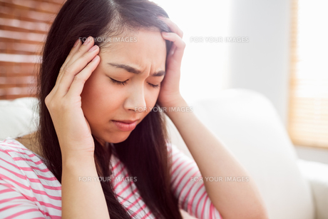 Asian woman getting headache on couchの写真素材 [FYI00486402]