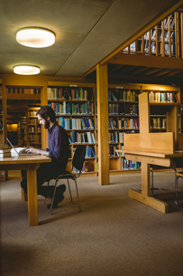 Hipster student studying in libraryの写真素材 [FYI00486405]