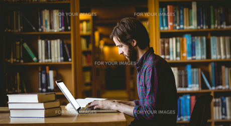 Hipster student studying in libraryの写真素材 [FYI00486408]