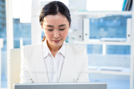Focused businesswoman on her computerの写真素材 [FYI00486433]
