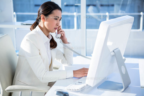 Smiling businesswoman using computer and telephoneの写真素材 [FYI00486438]