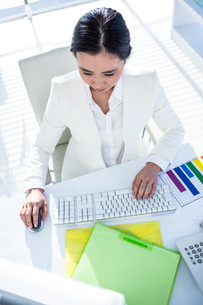 Businesswoman using her pc with documentsの素材 [FYI00486443]