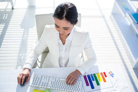 Businesswoman using her pc with documentsの素材 [FYI00486444]
