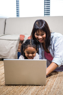 Happy young mother using laptop with her daughterの写真素材 [FYI00486450]