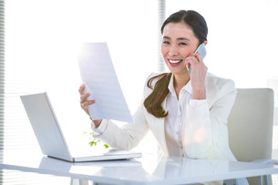 Smiling businesswoman with document phoningの写真素材 [FYI00486462]