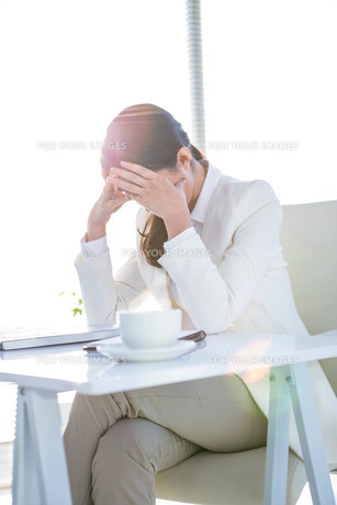 Worried businesswoman holding her headの写真素材 [FYI00486463]