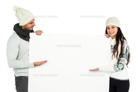 Smiling couple showing white sheetの写真素材 [FYI00486466]