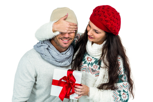 Smiling woman covering partners eyes and holding giftの写真素材 [FYI00486482]