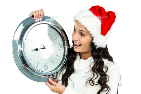 Attractive woman with christmas hat holding clockの写真素材 [FYI00486485]
