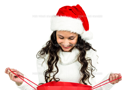 Happy woman with christmas hat looking in red shopping bagの素材 [FYI00486488]