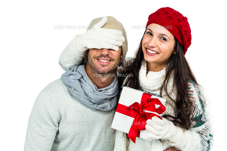 Smiling woman covering partners eyes and holding giftの写真素材 [FYI00486494]