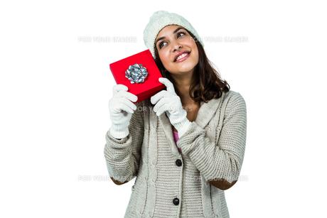Festive brunette holding a giftの素材 [FYI00486510]