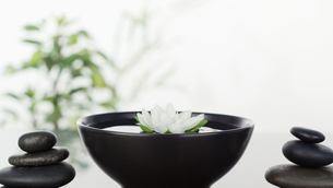 White flower floating in bowl in th ;iddleand two stacks of black pebbles on each sidesの素材 [FYI00486531]
