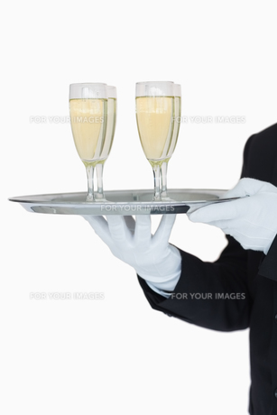 Waiter holding tray of champagne flutesの写真素材 [FYI00486545]