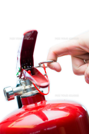 Hand pulling safety pin from fire extinguisherの写真素材 [FYI00486595]