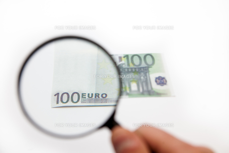 Hand holding magnifying glass over euro noteの写真素材 [FYI00486606]