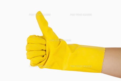 Female hand in yellow glove giving the thumbs upの素材 [FYI00486729]