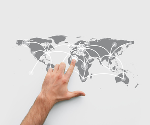 Finger pointing a map showing world connectionsの写真素材 [FYI00486738]