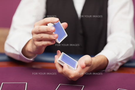 Dealer shuffling deck of cards in a casinoの写真素材 [FYI00486773]