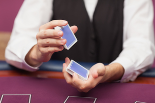 Dealer shuffling deck of cards in a casinoの写真素材 [FYI00486773]