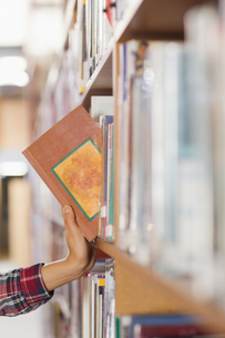 Close up of student taking book out of shelfの写真素材 [FYI00486780]