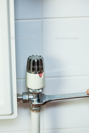 Close up of handyman repairing radiatorの写真素材 [FYI00486783]
