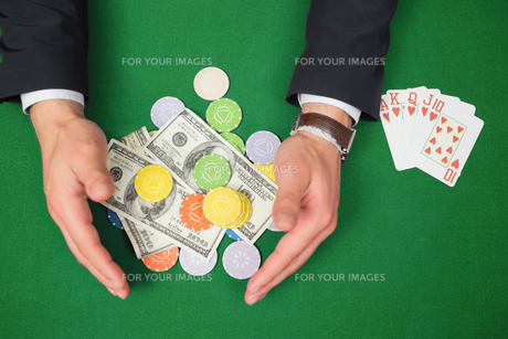 Hands grabbing dollars and chips from table beside royal flushの写真素材 [FYI00486790]