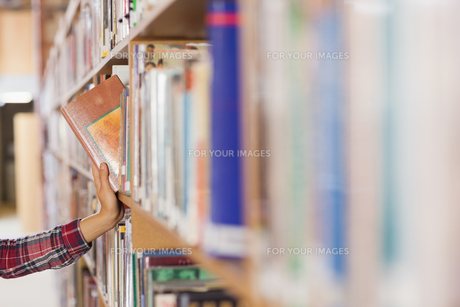 Pretty student taking book out of shelfの写真素材 [FYI00486800]