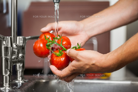 Kitchen porter washing tomatoesの素材 [FYI00486816]