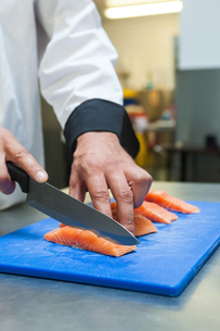 Close up of chef slicing raw salmon with sharp knifeの素材 [FYI00486818]