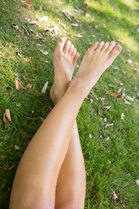 Close up of a womans crossed legs lying on the grassの素材 [FYI00486820]