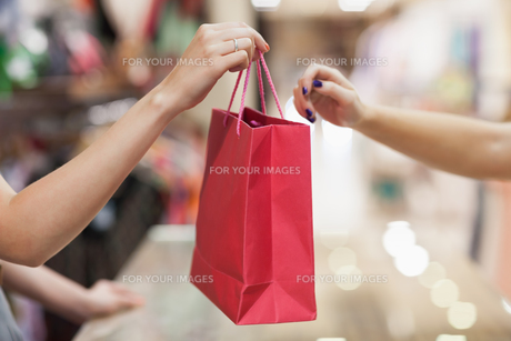 Woman handing over shopping bagの素材 [FYI00486845]