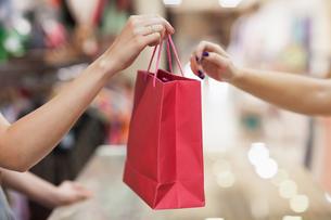 Woman handing over shopping bagの写真素材 [FYI00486845]