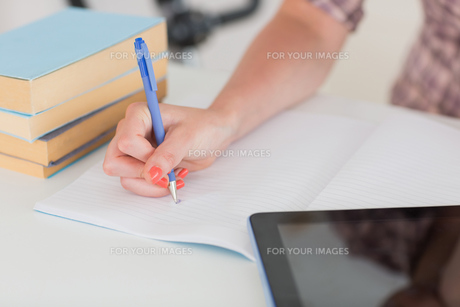 Woman writing on notepad with tablet pcの写真素材 [FYI00486846]
