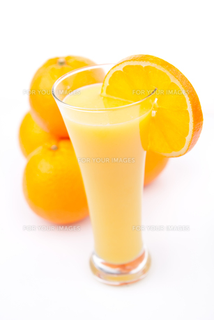 Full glass of orange juice placed near a heap of orangesの写真素材 [FYI00486880]