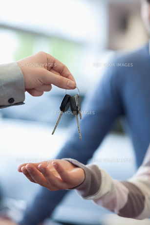 Salesman holding keys over the hand of a customerの写真素材 [FYI00486956]