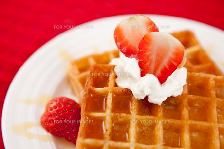 Half cut strawberry and whipped cream on a white plateの写真素材 [FYI00486959]