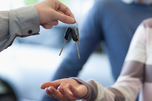 Car dealer giving keys to a customerの写真素材 [FYI00486978]
