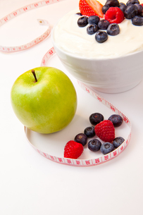 Apple and bowl of berries cream and a tape measureの写真素材 [FYI00486988]